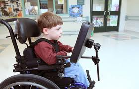 Young boy in wheelchair using touch screen