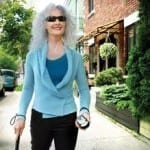 woman with sunglasses walking with a cane and a handheld talking gps unit