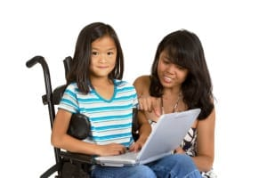 A girl in a wheelchair with a laptop. Her mother is looking at the screen with her.