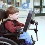 young child in wheelchair smiling using an AAC device