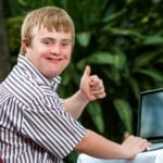 This is a picture of a handicapped student doing thumbs up sign next to laptop outdoors.