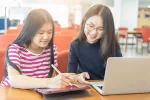 Two girls are looking at a tablet together.